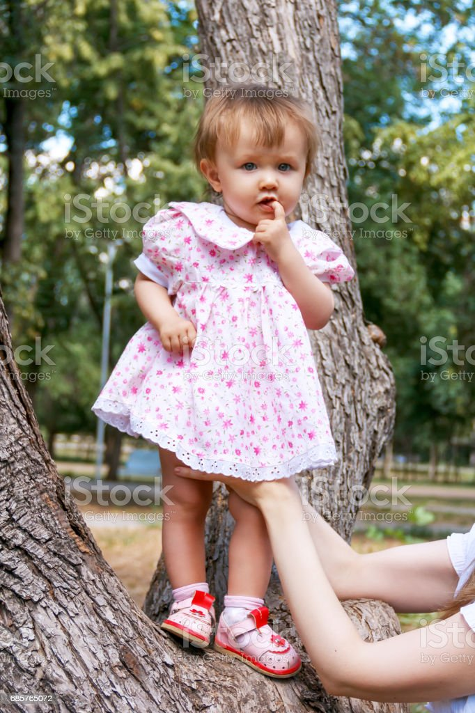 Cute infant in pink dress suckle finger royalty free stockfoto