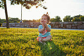 Beautiful and cheerful young baby girl sitting on the grass, enjoying the day at a park.