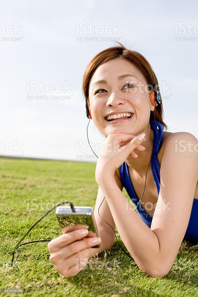 Cute Japanese woman listening to music royalty-free stock photo