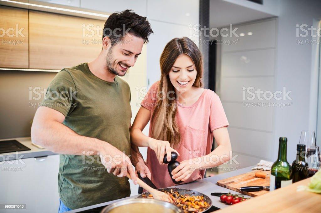 Süße fröhliche Paar zusammen zu kochen und Würze, Essen, lachen und Zeit miteinander zu verbringen, in der Küche - Lizenzfrei Arbeitsplatte Stock-Foto