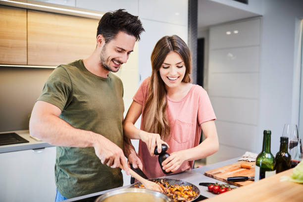 cute joyful couple cooking together and adding spice to meal, laughing and spending time together in the kitchen - cooker happy imagens e fotografias de stock