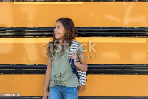 A cute, young junior high school girl poses by the school bus for a picture on the first day of school.