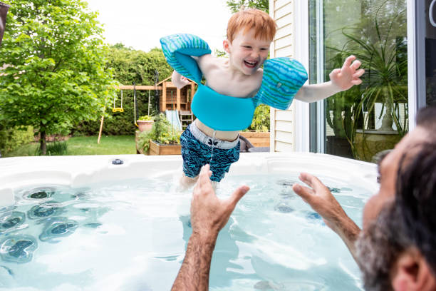 Cute Kid and Father in the Hot Tub in the Backyard in Summer stock photo
