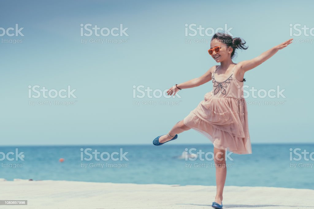 Beautiful girl on beach holiday standing at the quay and staring the...