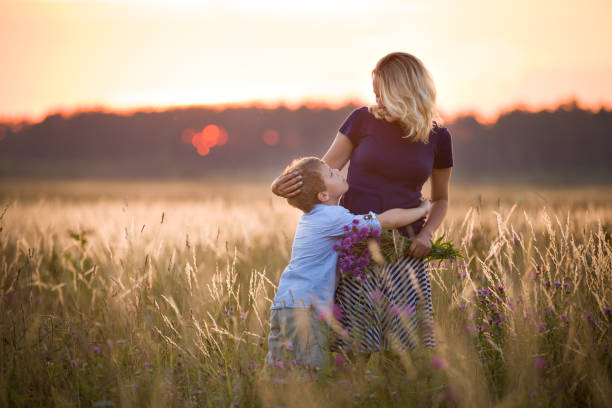Cute kid boy hugging his mother on a summer meadow on beautiful summer sunset. Happy family together. Mum and child. Motherhood and childhood. Family walking in the field. Outdoors. Cute kid boy hugging his mother on a summer meadow on beautiful summer sunset. Happy family together. Mum and child. Motherhood and childhood. Family walking in the field. Outdoors. Mother Nature stock pictures, royalty-free photos & images