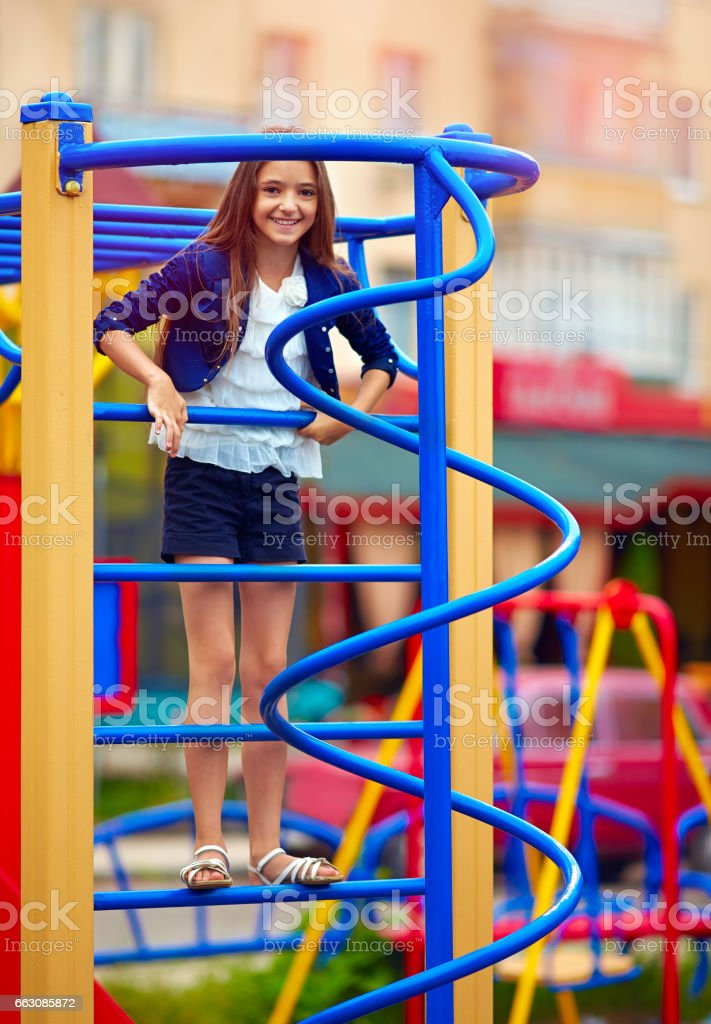 cute kid, girl climbs on the stile at playground stock photo