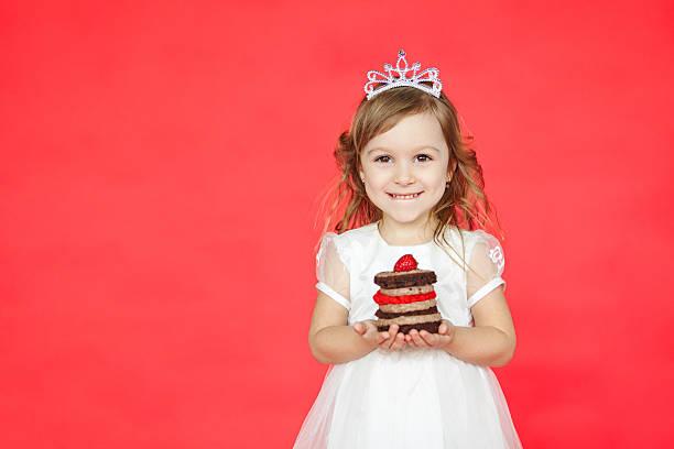 niedlich kleines kind mädchen halten köstliche mini-kuchen - prinzessinnen torte stock-fotos und bilder