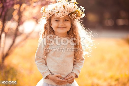 istock Cute kid girl posing in sun light 600100700