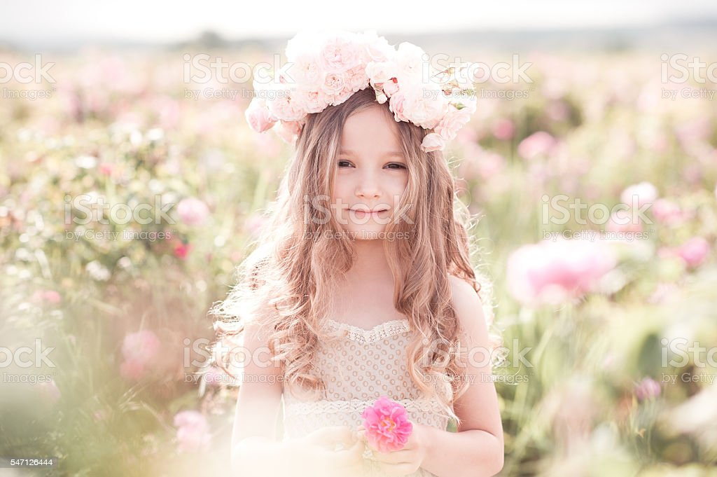 Cute kid girl posing with flowers outdoors stock photo