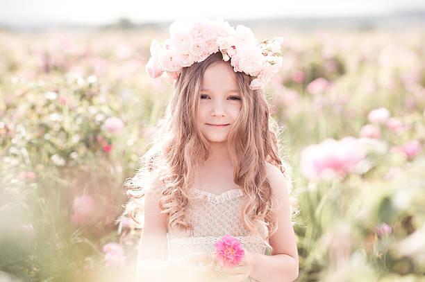 cute kid girl posing with flowers outdoors - mini amusementpark stockfoto's en -beelden