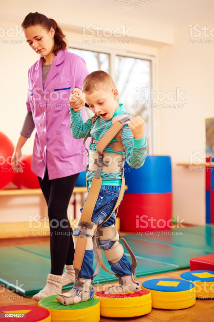 cute kid having physical musculoskeletal therapy in rehabilitation center - foto stock