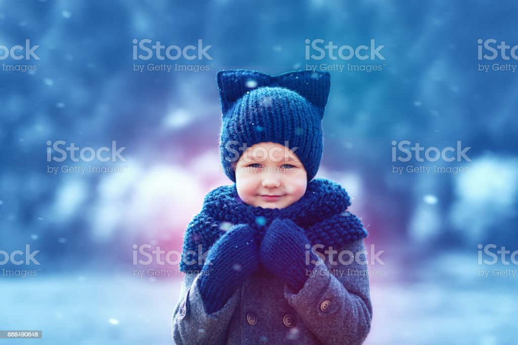 a9402cbb6a Cute kid in knitted wear and felted coat under winter snow - Stock image .