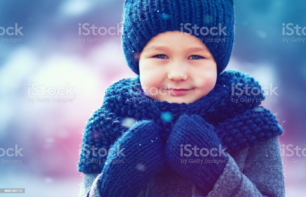 cute kid in knitted wear and felted coat under winter snow stock photo