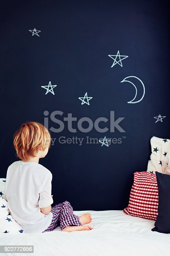 istock cute kid in pajamas dreaming , while sitting in bed and looking on chalkboard wall 922772656