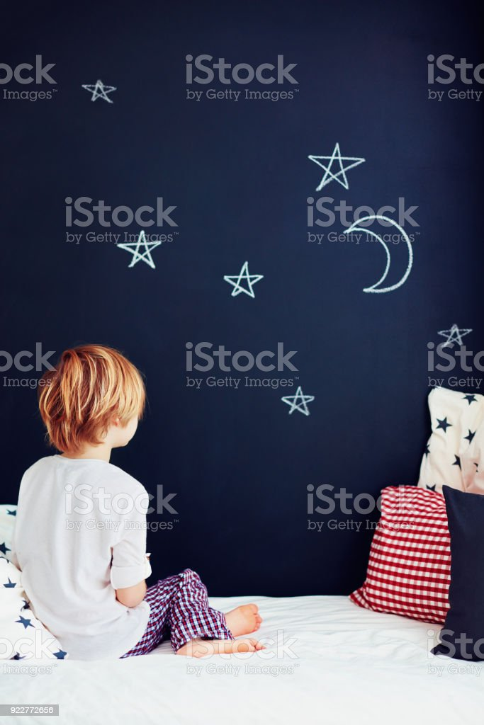 cute kid in pajamas dreaming , while sitting in bed and looking on chalkboard wall stock photo