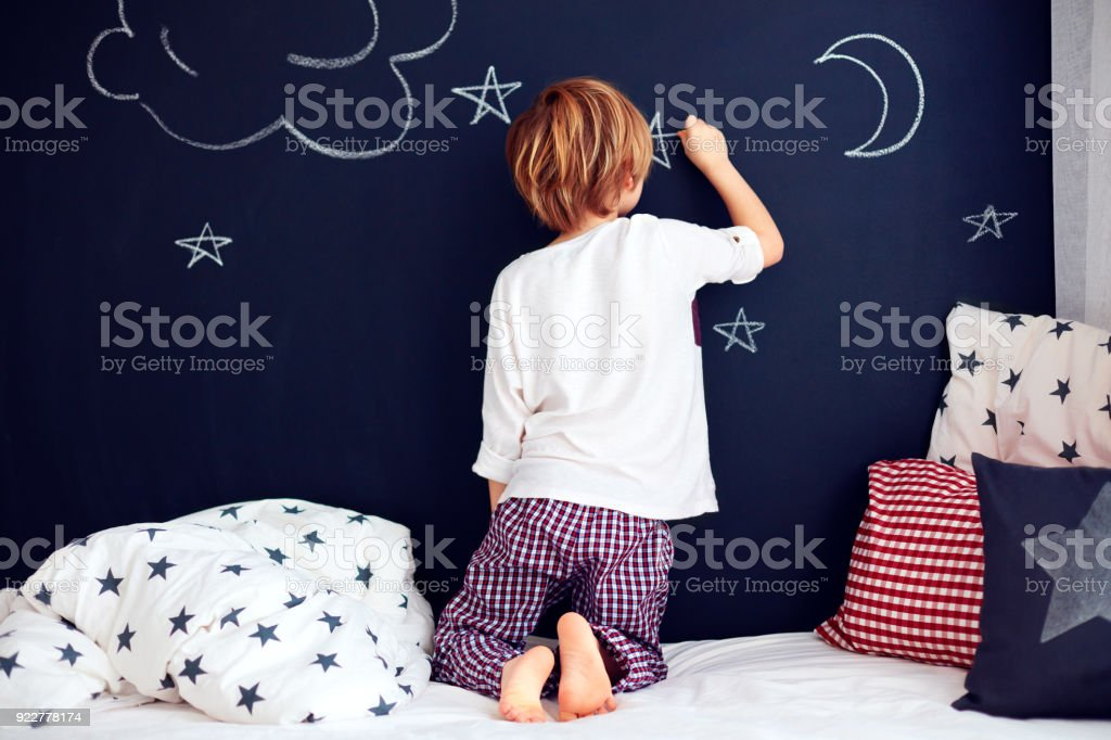 cute kid in pajamas painting chalkboard wall in his bedroom stock photo