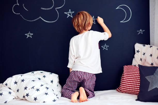 可愛的孩子在睡衣畫黑板牆在他的臥室 - kids drawing 個照片及圖片檔