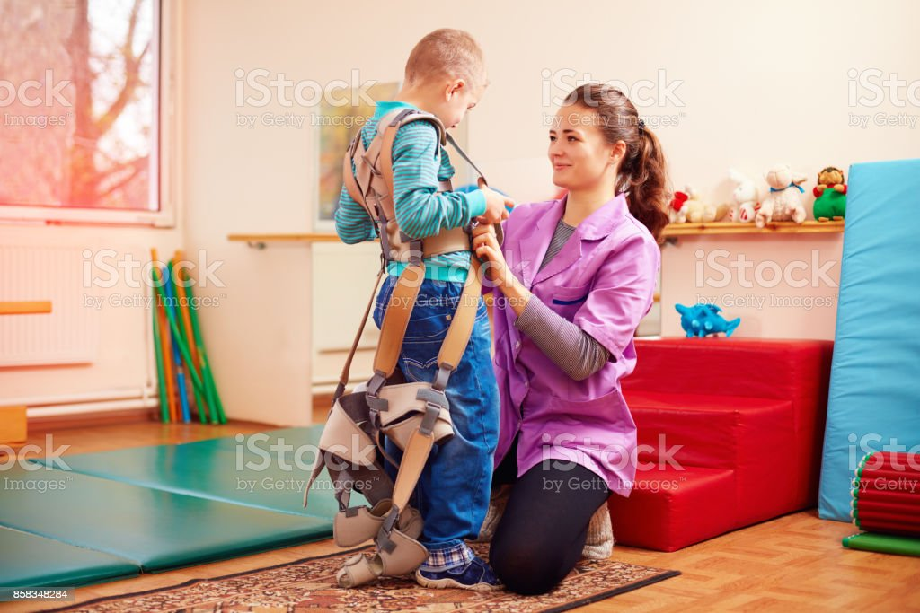 cute kid is going to have physical musculoskeletal therapy in rehabilitation center - foto stock