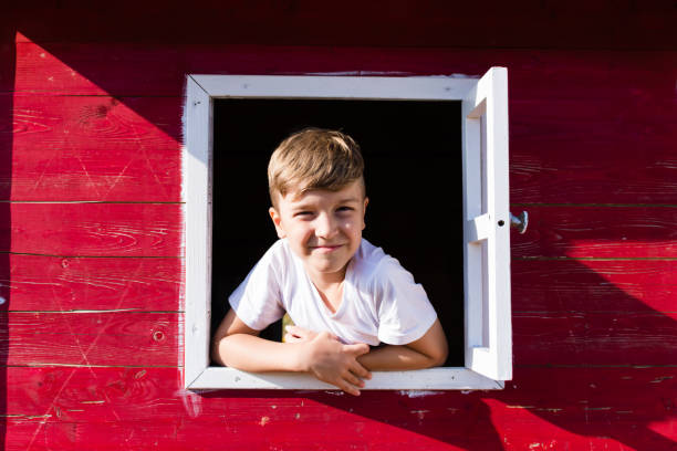 Cute kid looking through the window of a playhouse.
