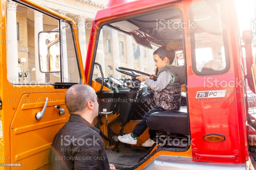 Cute Kid Playing In Fire Truck Pretending To Be Firefighter