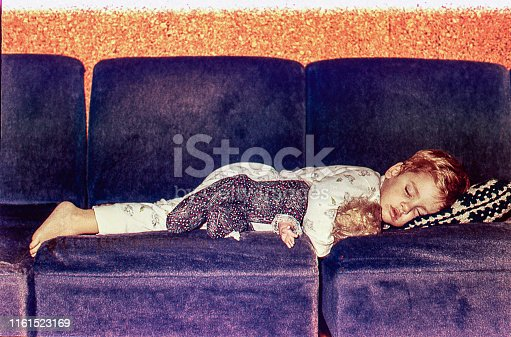 Vintage image of a cute kid sleeping on a sofa with her doll.