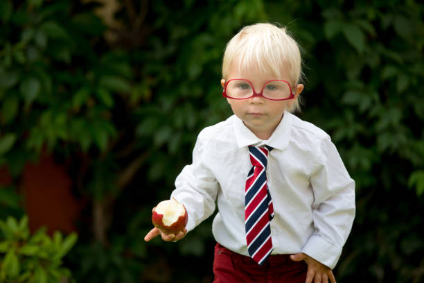 cute kid, wearing glasses and eating apple, dressed for first day of school or kindergarden - nerd boy eating stock photos and pictures