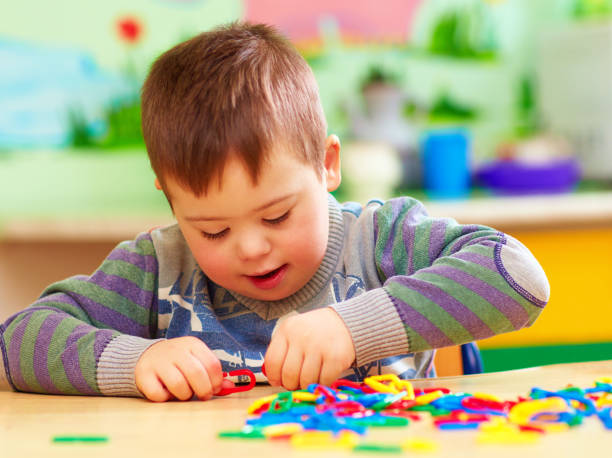 cute kid with down's syndrome playing in kindergarten cute kid with down's syndrome playing in kindergarten autism stock pictures, royalty-free photos & images