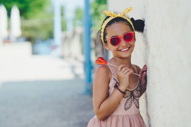 Cute kid with heart-shaped lollipop stock photo