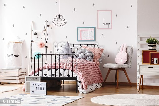 Colorful pillows on knit pink blanket on bed in cute kids bedroom with posters on wall