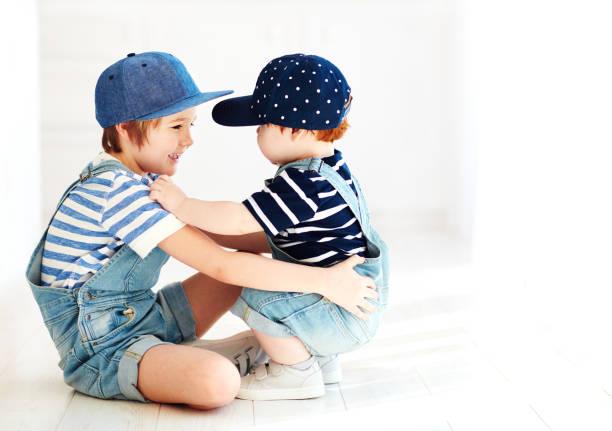 niedlichen kinder, brüder im denim-overalls, kommunikation, drinnen - jeans overall stock-fotos und bilder