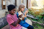 Cute preteen kids cuddling baby rabbits sitting outside near an old barn in springtime. She is caucasian wearing a jean dress. He is african-american wearing a pink t-shirt. Horizontal waist up outdoor shot with copy space. This was taken in Quebec, Canada.