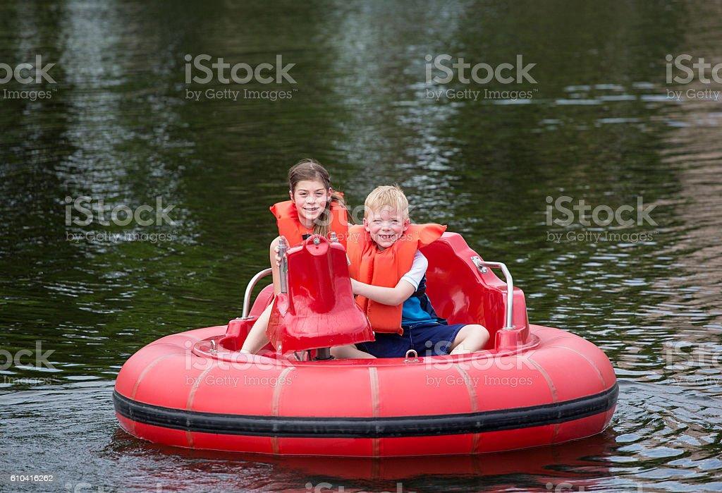 Cute kids having fun riding bumper boats on a lake stock photo