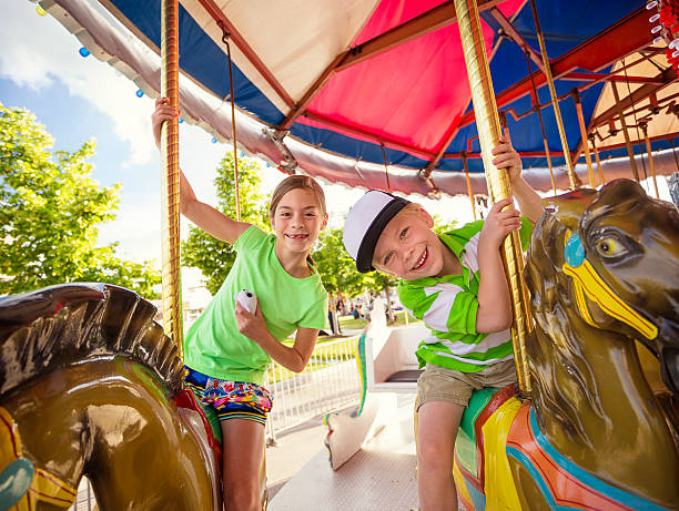 Cute kids having fun riding on a colorful carnival carousel Two cute kids enjoying a ride on a fun carnival carousel. A happy girl and boy are Smiling and having fun together at the summer carnival carnival children stock pictures, royalty-free photos & images