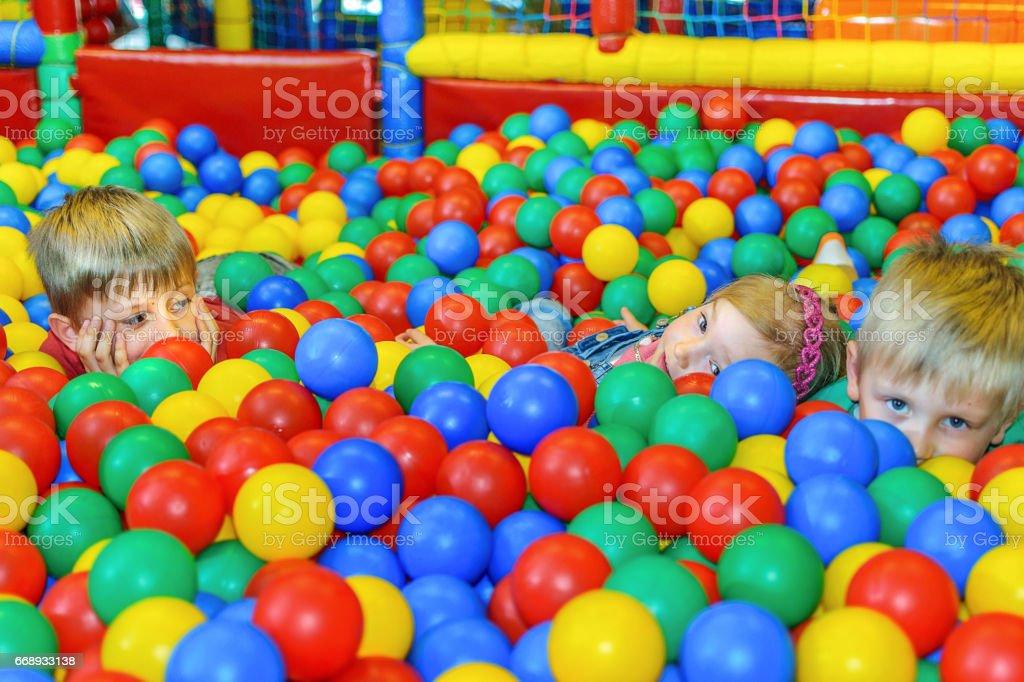 Lindos filhos em uma piscina de bolas de esponja - foto de acervo