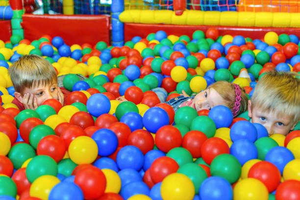 Enfants mignons dans une piscine à balles éponge - Photo
