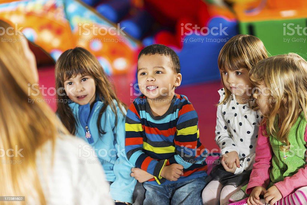 Cute kids listening to the nursery teacher stock photo