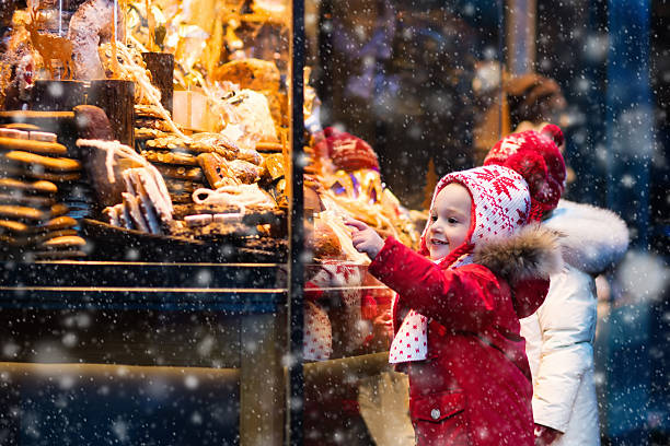 cute kids looking at candy and pastry on christmas market - weihnachtsfeier münchen stock-fotos und bilder