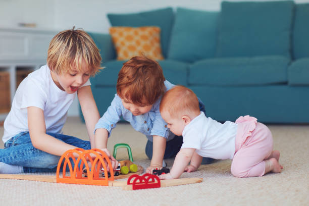 cute kids, siblings playing toys together on the carpet at home stock photo