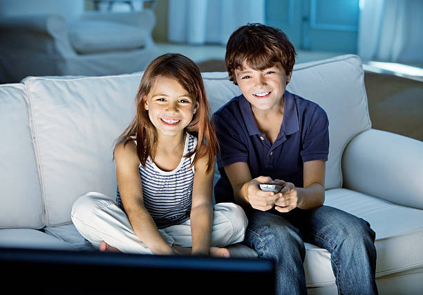 Cute kids watching television stock photo