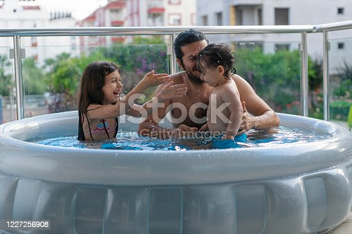 Cute kids with father having fun in an inflatable swimming pool in the balcony at home