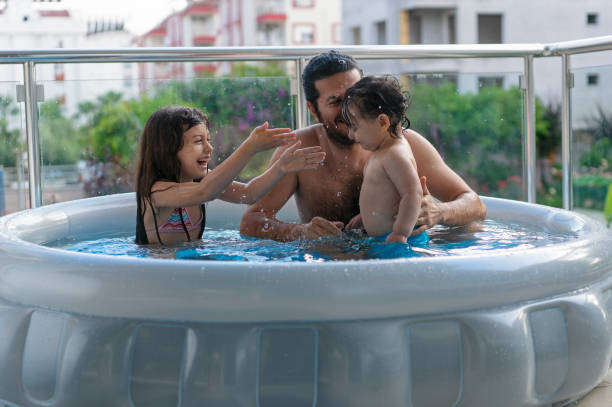 Cute kids with father having fun in an inflatable swimming pool in the balcony at home stock photo