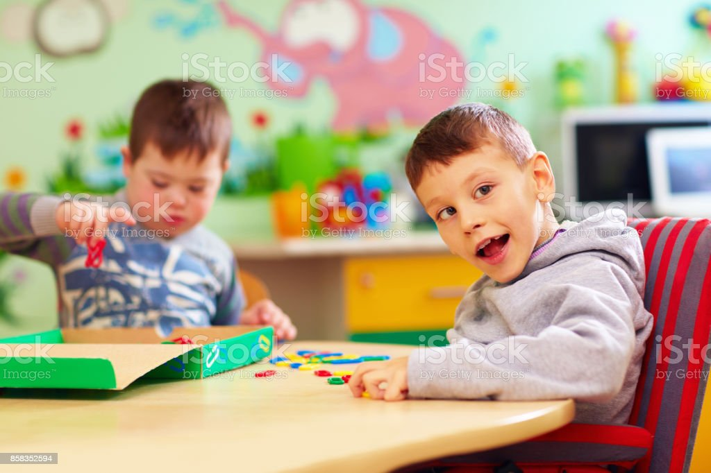 cute kids with special needs playing with developing toys while sitting at the desk in daycare center stock photo