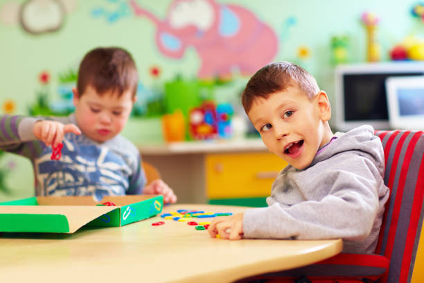 cute kids with special needs playing with developing toys while sitting at the desk in daycare center - crianças todas diferentes imagens e fotografias de stock