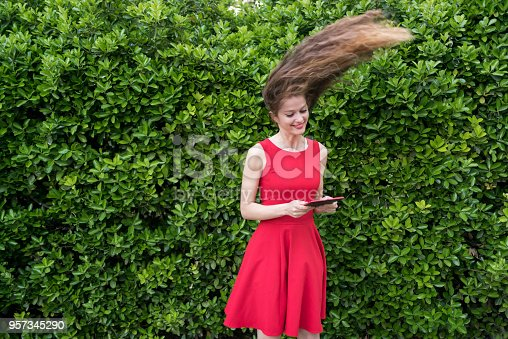 538883870istockphoto Cute lady in red amazed by something on her tablet 957345290