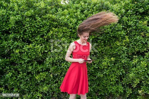 538883870istockphoto Cute lady in red shocked by something on her tablet 957345418