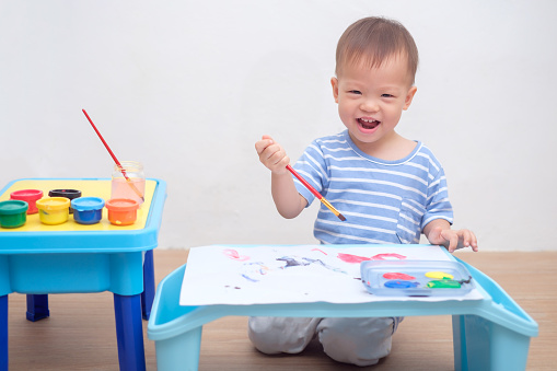 1042756824 istock photo Cute lAsian 18 months / 1 year old toddler boy child painting with brush & watercolors at home 968303126