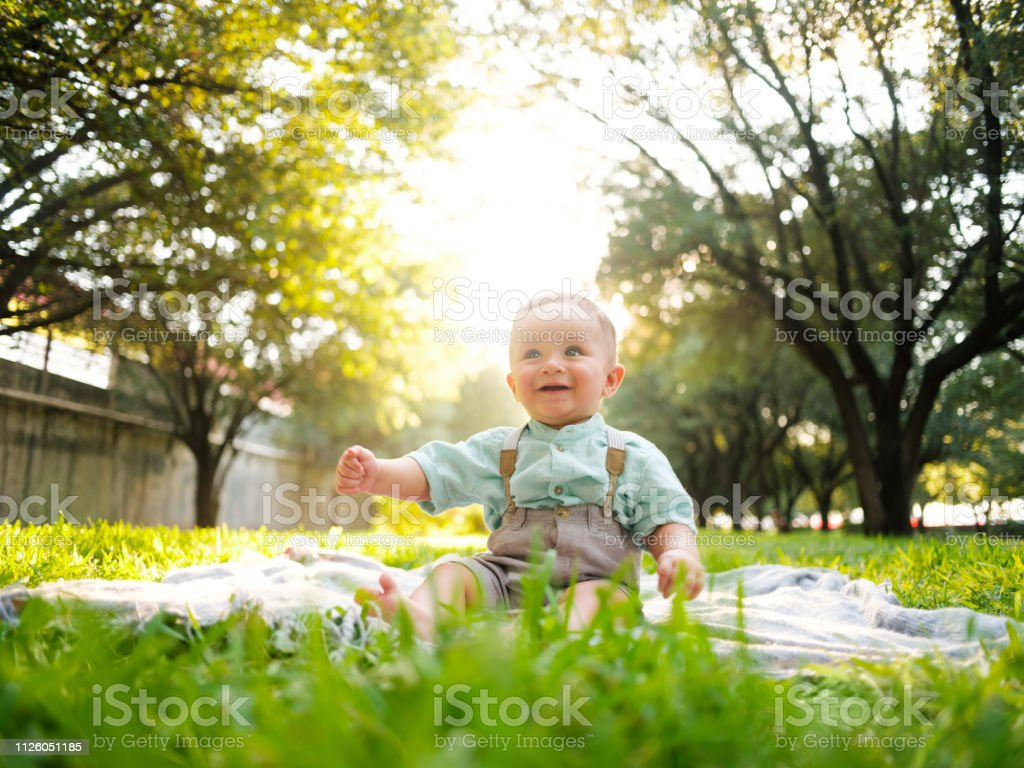 Cute latin baby boy sitting on blanket outdoors and looking away stock photo