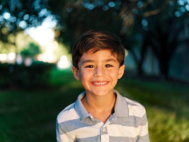 Cute latin boy looking at camera and smiling stock photo