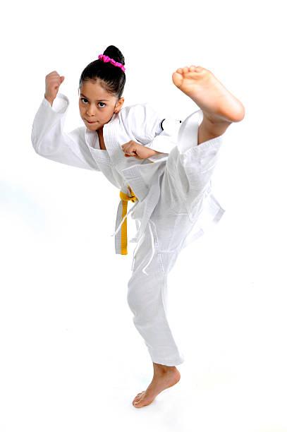 hübsche latin-mädchen im kimono training karate kick attack - asiatischer kampfsport stock-fotos und bilder