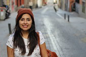 Cute Latin woman smiling on the street.